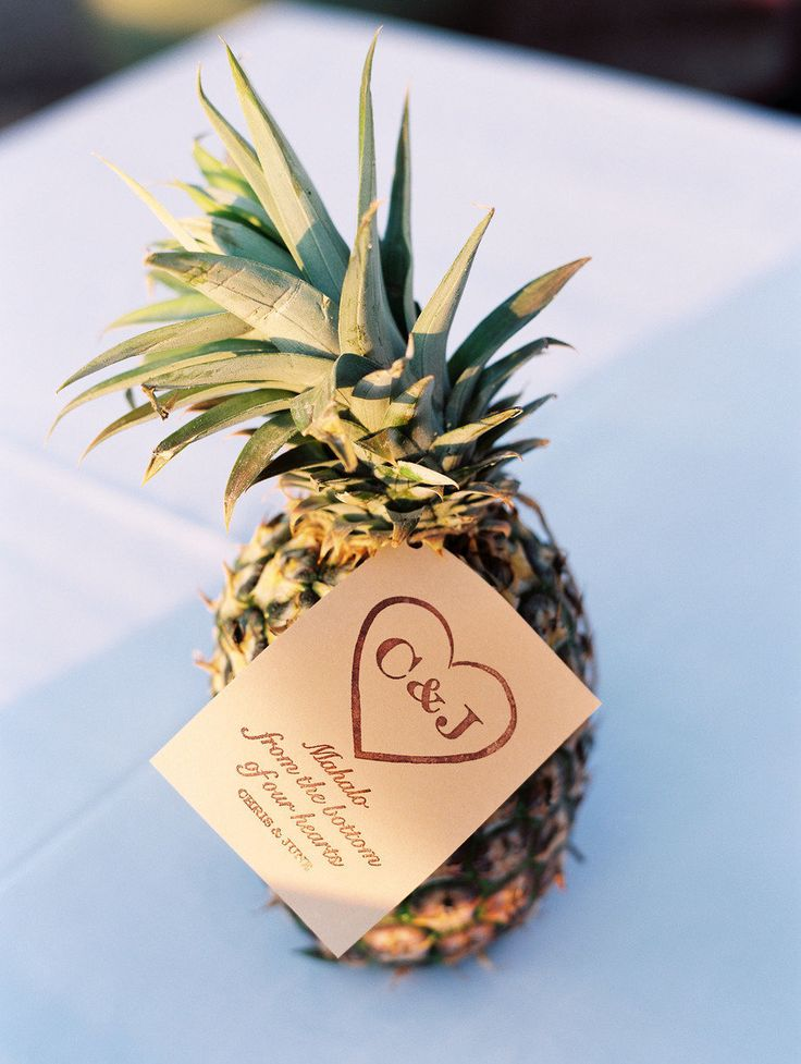 a pineapple with a gift tag is a perfect tropical wedding favor