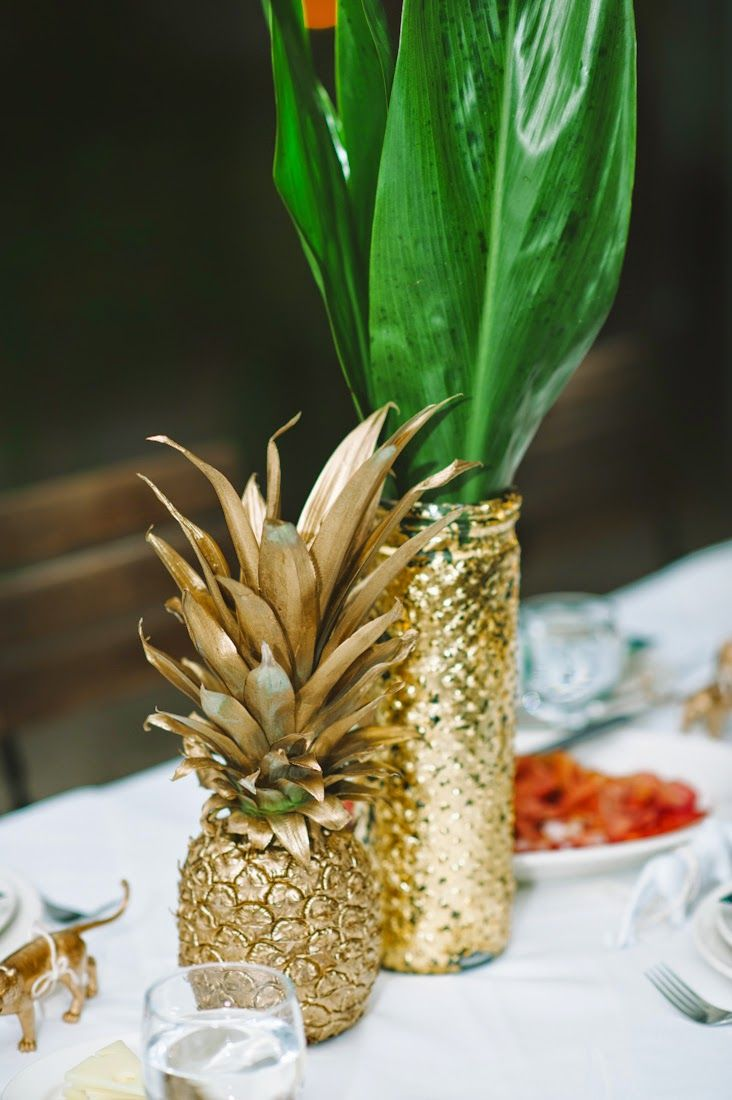 a gilded pineapple and a gold vase with tropical leaves is a chic and refined glam wedding centerpiece for a modern wedding