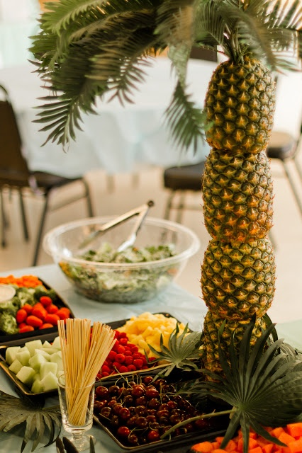 a berry and fruit table decorated with a pineapple tree - lots of pineapples stacked and topped with leaves is ideal