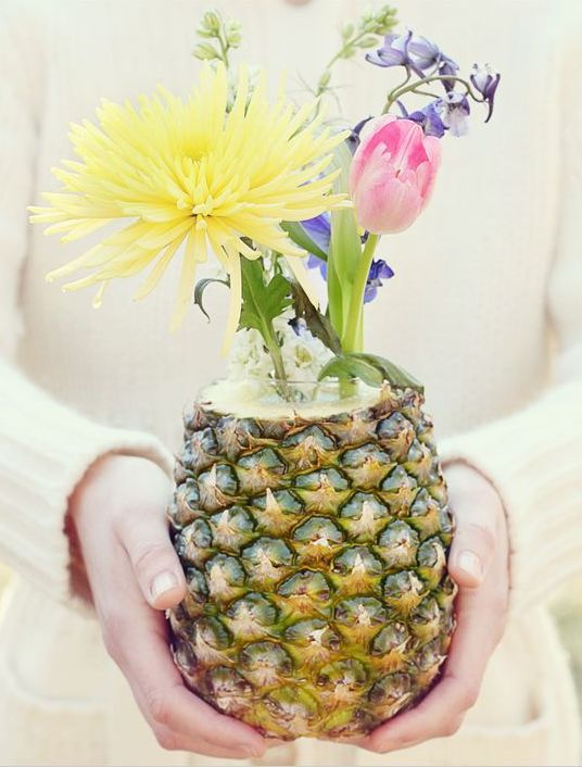 a pineapple as a vase, with bright blooms is a very cool idea for a wedding centerpiece