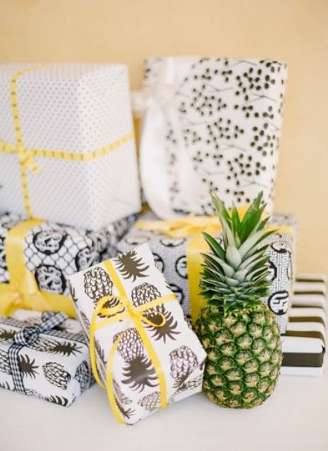 wedding favors wrapped into paper with pineapple prints is a very cool idea for a tropical wedding
