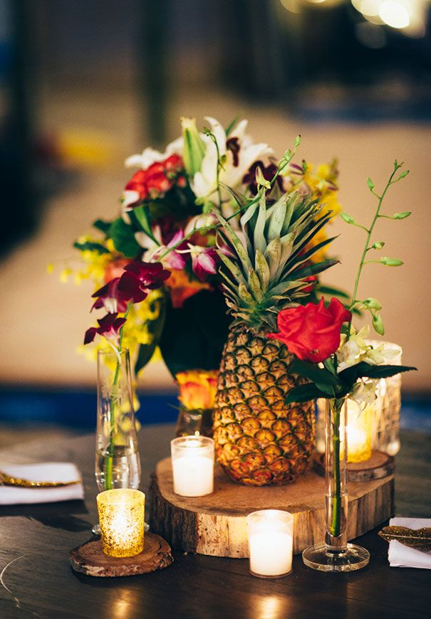 a bright wedding centerpiece of candles, bold blooms and greenery and a pineapple is ideal for a modern and refined tropical wedding