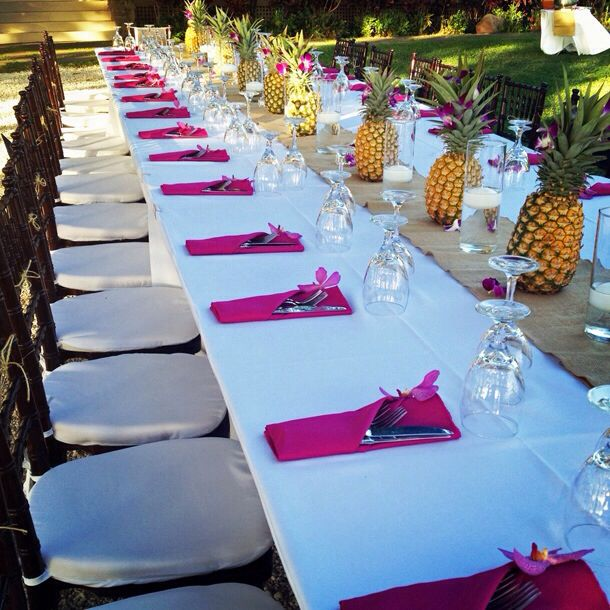 a bold wedding tablescape with fuchsia napkins, pineapples lining up the table and neutral linens