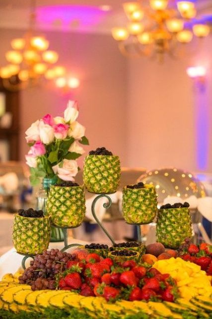 a fruit and berry table styled with trays, bowls and pineapples as vases for berries is very creative