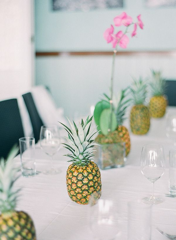 a minimalist tropical wedding tablescape with pineapples, orchids and all white everything is very chic