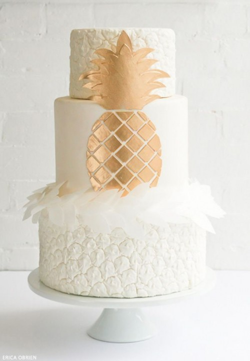 a white and copper wedding cake with a pineapple texture, white petals and a chic copper pineapple for a modern tropical wedding
