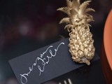 a glam and chic place setting with a gold pineapple and a black card is a very chic and refined idea