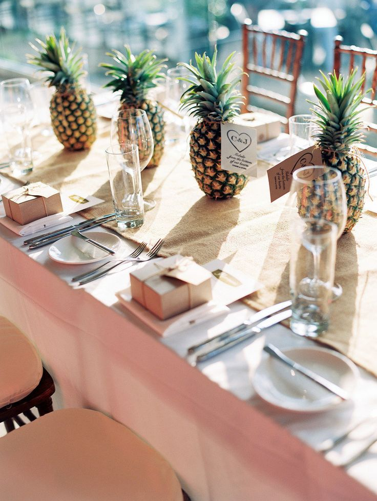 a neutral tropical wedding tablescape with a burlap runner, white porcelain and silver cutlery, pineapples are given as wedding favors