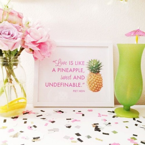 a bright and glam tropical wedding sign with pink printing and a pineapple, pink blooms and a green glass with a pink umbrella for tropical decor
