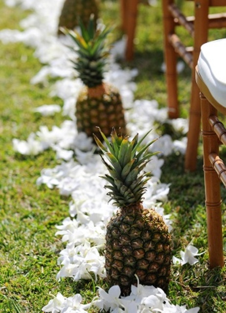 pineapples lining up the aisle and white tropical blooms are ideal to accent a wedding ceremony space
