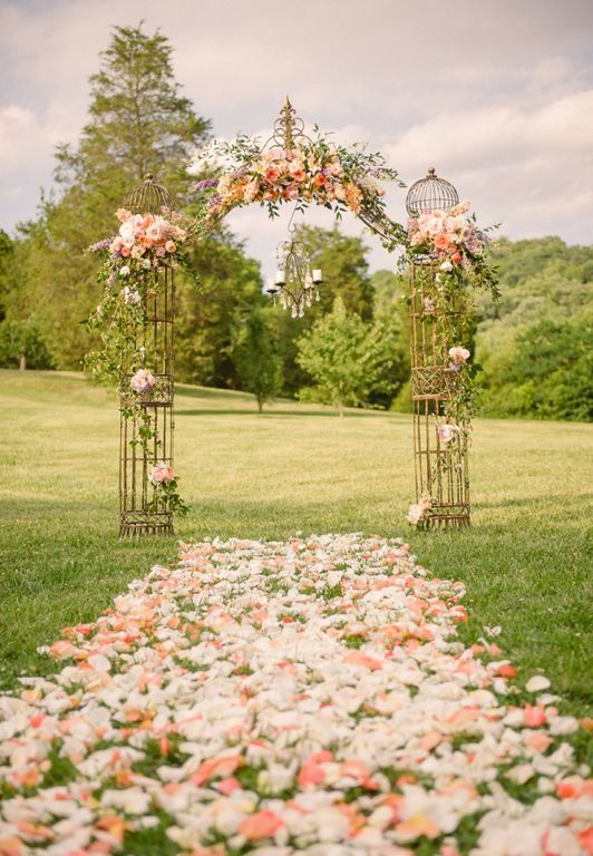 a romantic metal wedding arch decorated with pastel blooms and greenery and with pastel petals covering the aisle