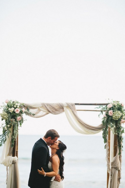 a coastal spring wedding arch decorated with neutral fabric, pink and white blooms and greenery