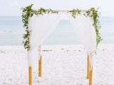 a fresh coastal spring wedding arch decorated with white fabric and greenery on top is classics
