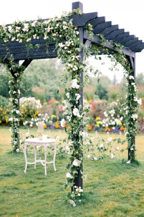 a black wedding arch interwoven with greenery and white blooms to refresh it and make it look like spring