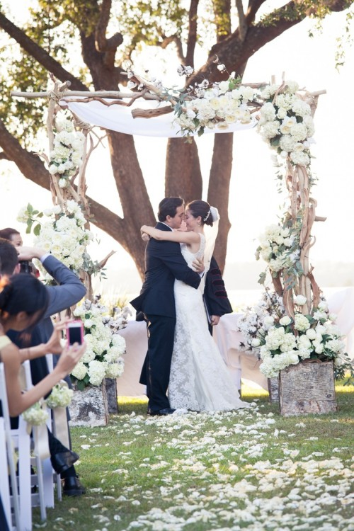a spring wedding arch made of driftwood and decorated with greenery and lush white blooms for spring