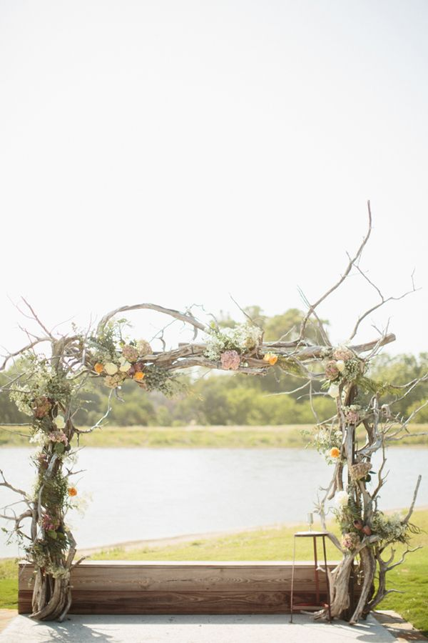 a driftwood spring wedding arch decorated with twigs and greenery and some pastel blooms