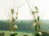 a spring wedding altar made of black vases and branch arrangements with greenery and white hydrangeas