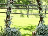 a woodland sprign wedding arch made of vine, with white blooms and greenery and lots of antlers
