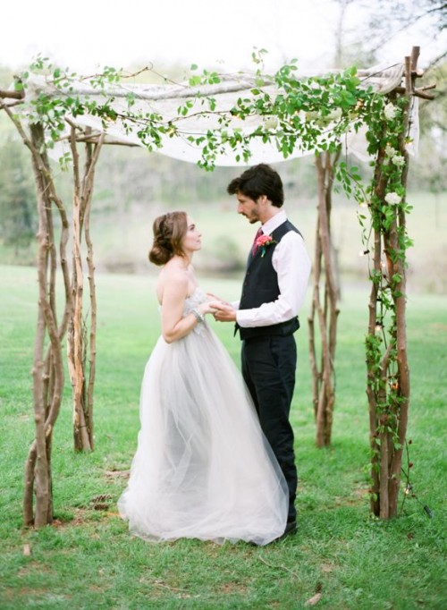 a cool and fresh spring wedding arch made of branches, fresh greenery and some sheer fabric on top looks very spring-like
