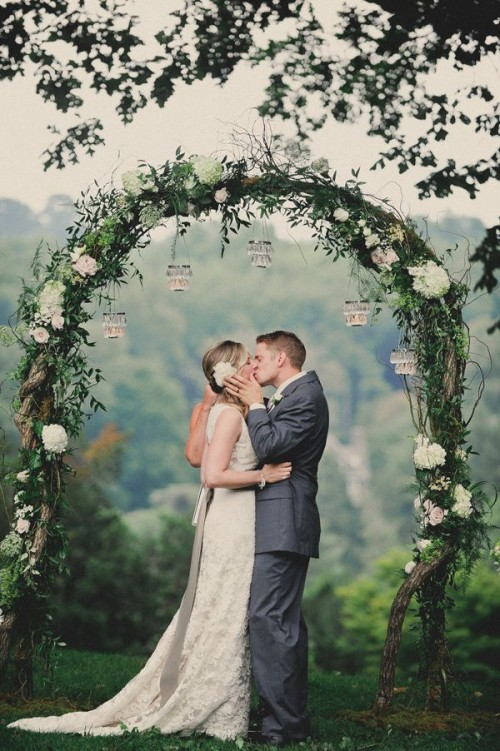 a vine spring wedding arch covered with greenery and white blooms and some candles hanging down is amazing