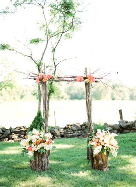 a wedding arch of branches decorated with bright coral pink and white blooms and some greenery for a colorful spring wedding