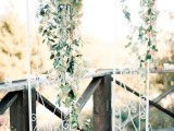 a delicate white metal arch decorated with greenery and peachy blooms feels and looks very spring-like