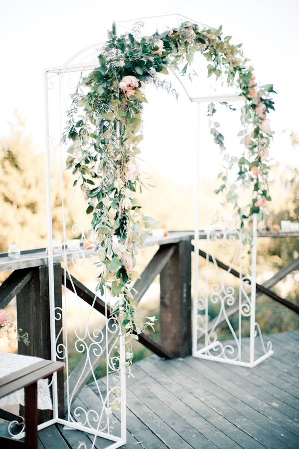 a delicate white metal arch decorated with greenery and peachy blooms feels and looks very spring like