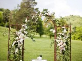 a rusty metal wedding arch decorated with lush greenery and white blooms looks sophisticated and beautiful