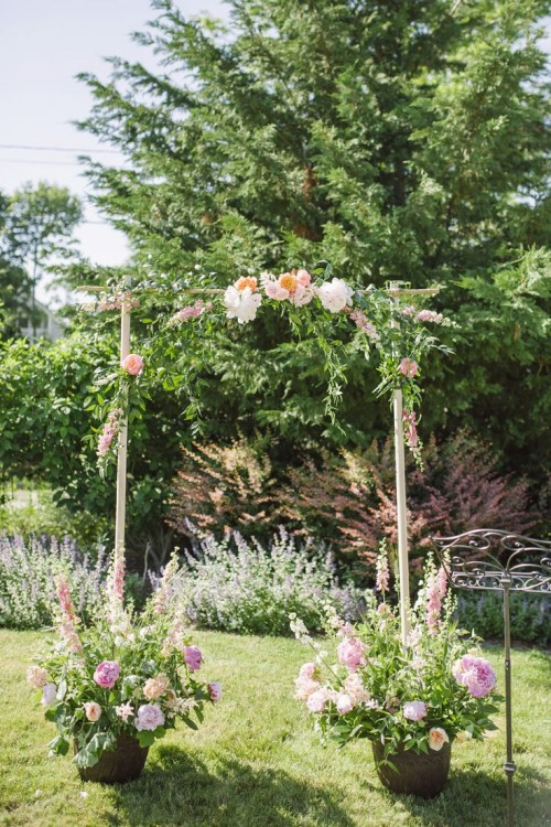 a spring wedding arch of branches decorated with greenery and blooms and put into large pots with flowers