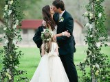 a simple and fresh spring wedding arch of greenery and some white blooms is all you need for a beautiful ceremony
