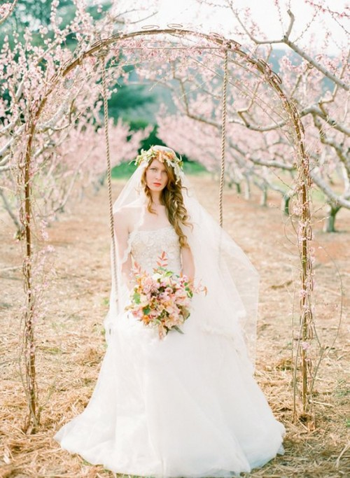 a vine wedding arch decorated with cherry blossom is a real spring-like dream