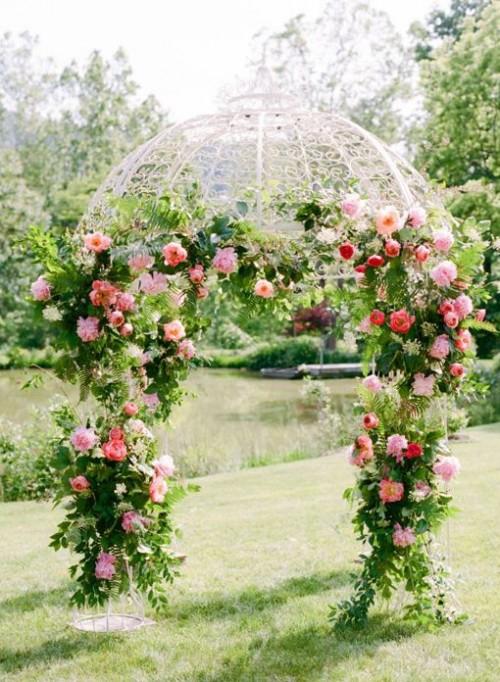 a lush and colorful sprign wedding arch done with greenery and pink blooms all over for a bright spring wedding