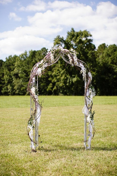 a refined wedding arch with vines, white fabric, greenery and white blooms for a spring wedding