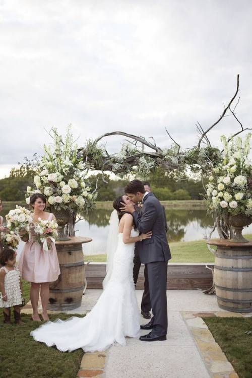 a creative wedding arch composed of two greenery and white bloom arrangements in vases placed on barrels and a piece of driftwood on them