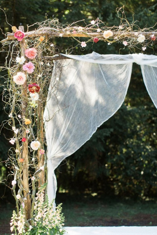 a delicate spring wedding arch interwoven with bright blooms and some vines and decorated with white fabric