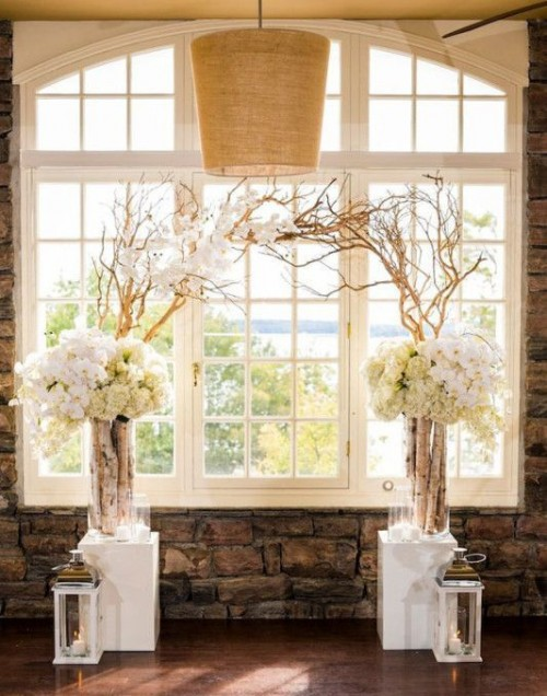 white stands with driftwood branches and lush white florals plus white lanterns create a feeling of a blooming area indoors