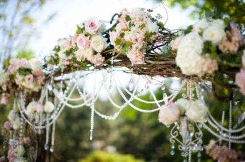 a vine wedding arch decorated with pink and white blooms, with greenery and crystals looks very romantic