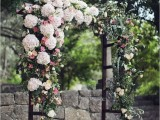 a lush wedding arch covered with lush florals on one side and with greenery for a spring feeling