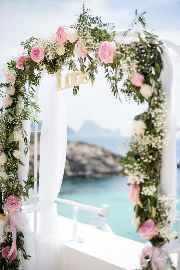 a spring wedding arch decorated with greenery, pink and white blooms, white fabric and the word LOVE