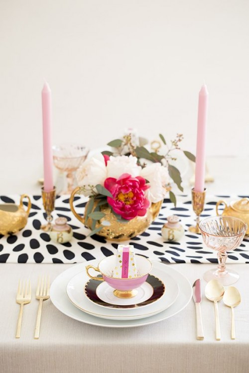 a glam wedding centerpiece of a gold bowl with white and fuchsia blooms and greenery plus pink candles in gold candleholders