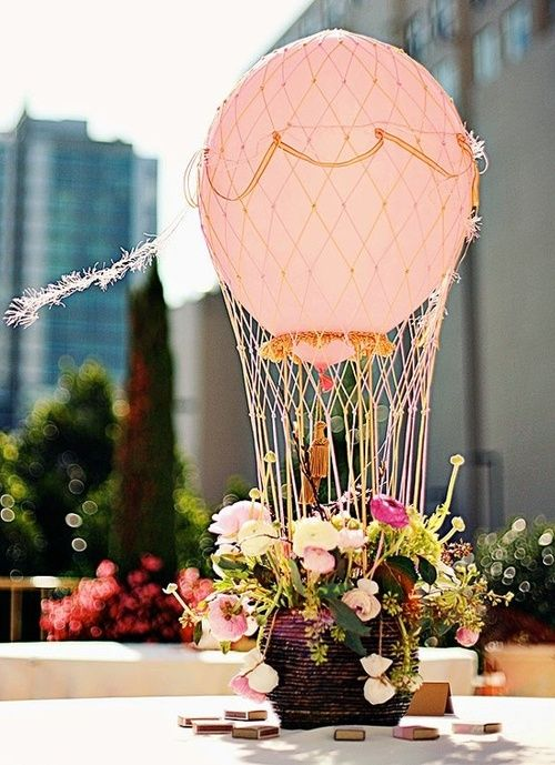 a cute Valentine's Day wedding centerpiece styled as a hot air balloon - in pink, with greenery and pink blooms is very chic