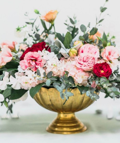 a beautiful Valentine's Day wedding centerpiece of a gold bowl with pink, red and blush blooms and greenery is pure elegance and chic