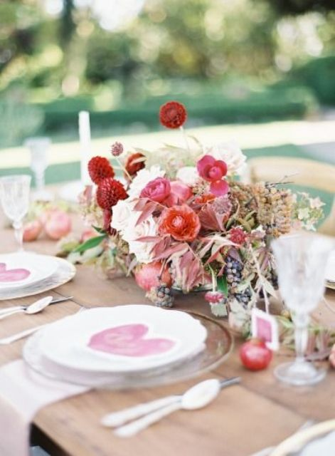 a chic Valentine's Day wedding centerpiece of red and white blooms and dried herbs and leaves is a stylish idea to rock