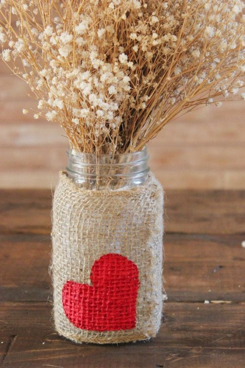 a jar with a burlap wrap with a heart and some dried blooms is a pretty rustic Valentine's Day centerpiece