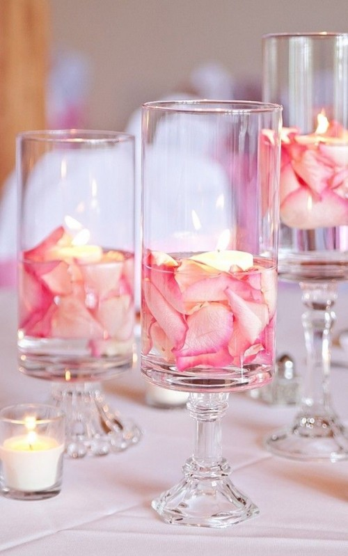 a cluster Valentine centerpiece of tall glasses with pink petals and floating candles is a very fresh and budget-friendly idea
