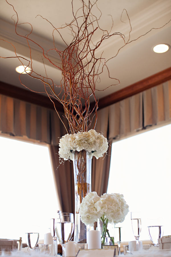 an elegant and formal winter wedding centerpiece of white blooms and tall branches in a vase