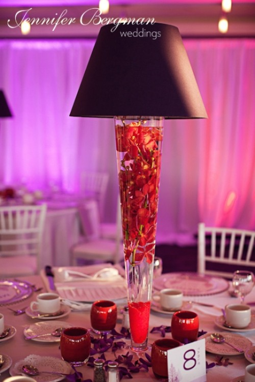 a unique winter wedding centerpiece of a lamp with red blooms floating inside it