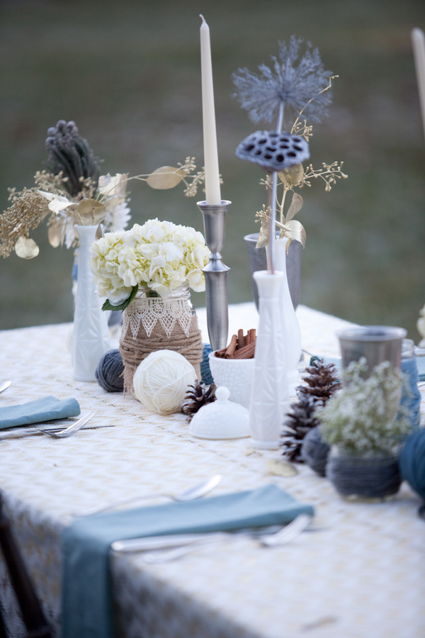 a whimsy and creative winter wedding centerpiece of yarn balls, pinecones, cinnamon bark in a bowl, neutral and gilded blooms