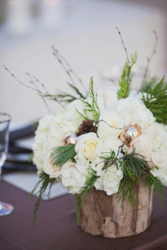 a rustic wedding centerpiece with white blooms, greenery, pinecones and ornaments