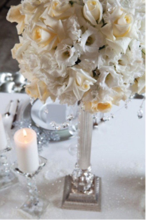 an elegant and formal white bloom centerpiece with pillar candles is a stylish idea to try